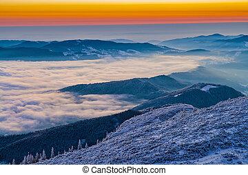 Winter sunrise on mountain mist in valley