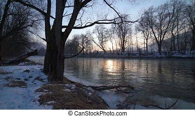 Winter sunrise on river bank