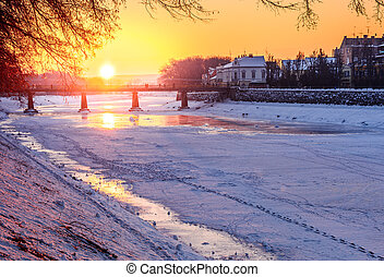 winter sunrise on the bank of ice covered river Uz. Sun over...