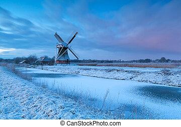winter sunrise over windmill in snow
