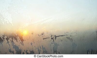 winter texture of shiny crystal hoarfrost pattern on car window glass under the sunlights during sunset in slow motion.