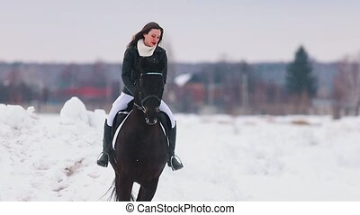 Winter time. A young woman with long hair riding a horse in...
