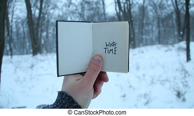 Winter time idea. Book and text. - Winter time. Hand holding...