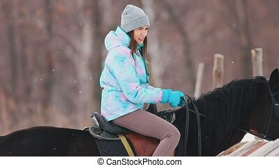Winter time, snowfall. A young woman riding a horse in a...