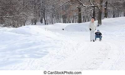 Winter time - Children having fun on a sleigh in the snow...