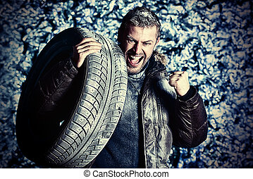 winter tires - Handsome brutal man dressed in winter clothes...