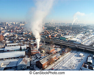 Winter town. Frosty sunny day in the city. Snow on the streets and smoke from the boiler rises. Frost and sun, a wonderful day