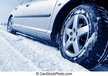 Close up of a cars tires on a snowy road - blue tone