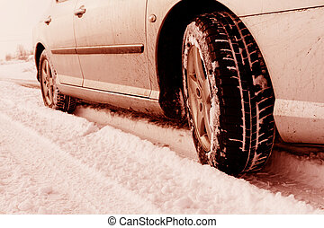 Close up of a cars tires on a snowy road - red tone