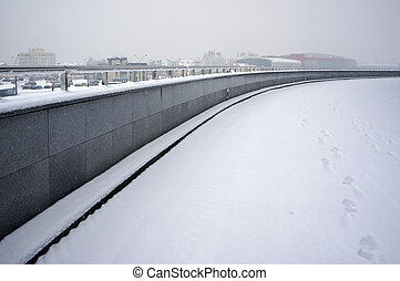 Winter urban scene. Snow, fog, footprints.