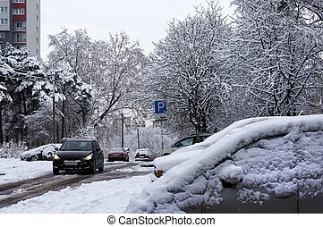 Winter urban scene. Snow on cars after snowfall.