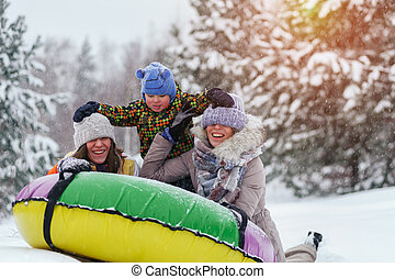 Winter vacation: people sledding on snow tubing. - Winter...