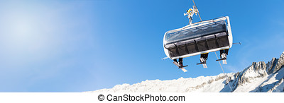 winter vacation - skiers in a chairlift against blue sky at ski resort with copy space