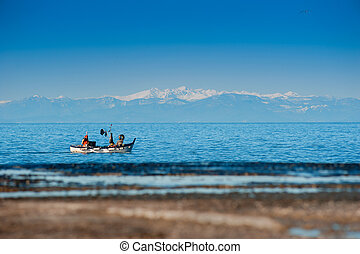 Winter view at the fishing boat in the sea with Mountains covered with snow.