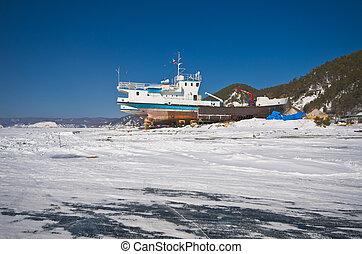 winter view of old rusty abandoned ship at frozen baikal lake