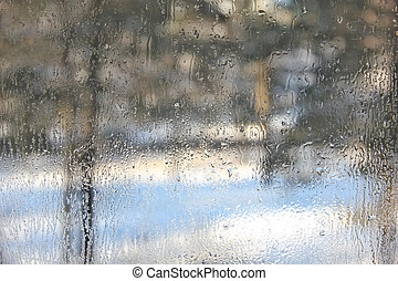Winter view through misted over glass of window.