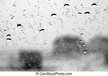 Winter view through window with focus on rain drops in black and white