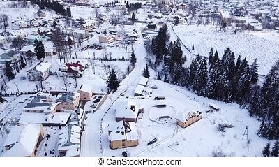 Winter village in a coniferous forest. Aerial view