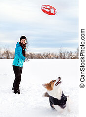 Winter walk in the snow, woman is playing flying disc or frisbee with her dog