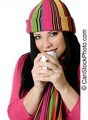 Winter Warmth - Cosy female in winter scarf and hat drinks a...