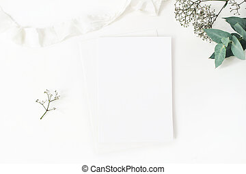 Winter wedding desktop stationery mockup. Blank greeting card, baby's breath Gypsophila flowers, eucalyptus branch and silk ribbon. White table background, top view. Christmas flatlay.