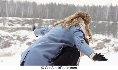 Couple enjoying their winter weekend together, guy holding his girlfriend piggyback