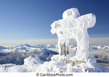 Winter Welcome - A snow covered Inuksuk greets visitors to...