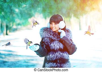 Winter woman on winter background. Woman Young girl feeding birds in the winter landscape.  Winter scene.