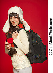 Winter woman tourist holding credit card