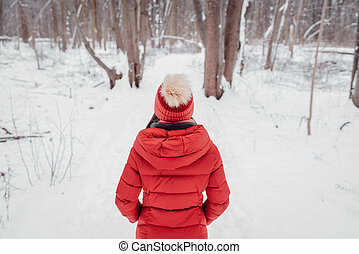 Winter woman walking in snow covered woods park. forest trail outdoors. View from behind of woman in red coat and beanie hat