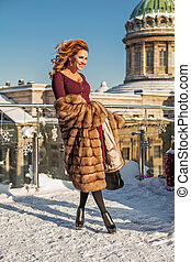 Winter woman with red curly hair outdoors