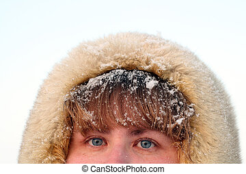 woman's blue eyes and hair under snow