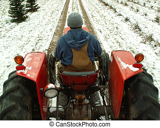 man driving tractor through the snow
