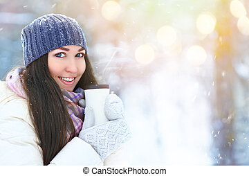 Winter young woman portrait. Beauty Joyful Model Girl holding thermocup with hot tea and smiling, having fun in winter park. Beautiful young woman laughing outdoors. Enjoying nature, wintertime