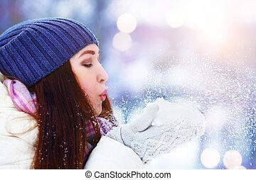 Winter young woman portrait. Winter girl blowing snow. Beauty Joyful Teenage Model Girl having fun in winter park. Beautiful young woman laughing outdoors. Enjoying nature.