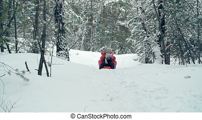 Wintertime Activities - Two kids riding toboggan down the...