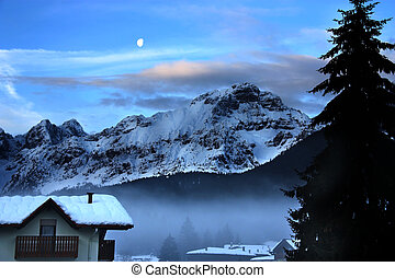 Wintertime landscape at dusk featuring snowy mountain moon and mountain hut