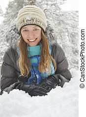 Wintet, lies the beautiful long-haired girl in the snow.