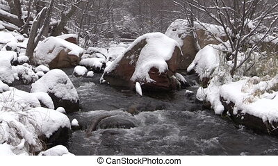 Wintry Landscape - a stream flows through a snow covered...