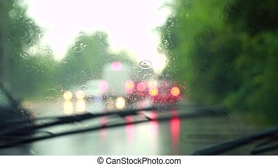 Wiper blades in slow motion wipe the glass from rain drops