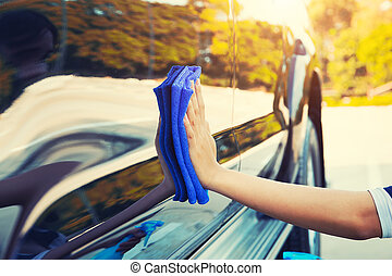 wiping on car - Women's hand wiping on car.