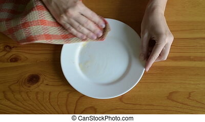 Wiping orange juice from the plate on a wooden table.
