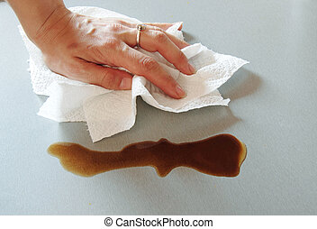 Wiping table - woman hand wiping spilled coffee with paper...