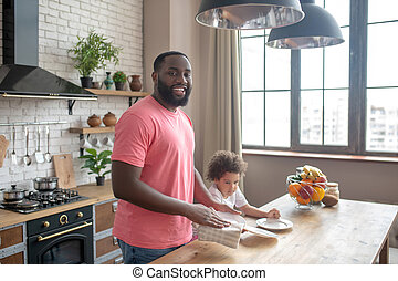 Tall dark-skinned man in a pink tshirt standing andsmiling widely while his kid helping to wipe the plate