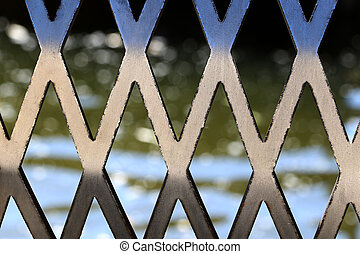 Wire fence or metal mesh on the background of water