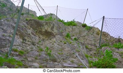 Wire mesh fences on the rocks of the mountain against rockfall