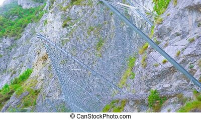 Wire mesh fence on the mountain rocks