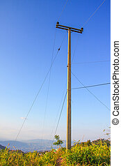 wire pole on mountain of countryside withe blue sky in...