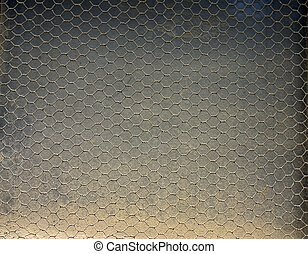 A dirty dusty window covered with a wire