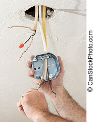 An electrician threading wire through a regulation fan ceiling box. Work being performed to code by licensed master electrician.